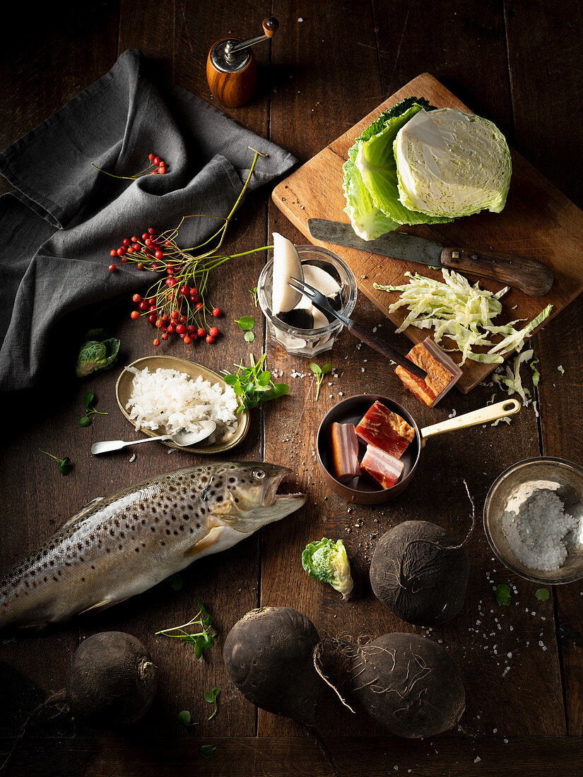 Still life with trout, bacon and winter vegetables