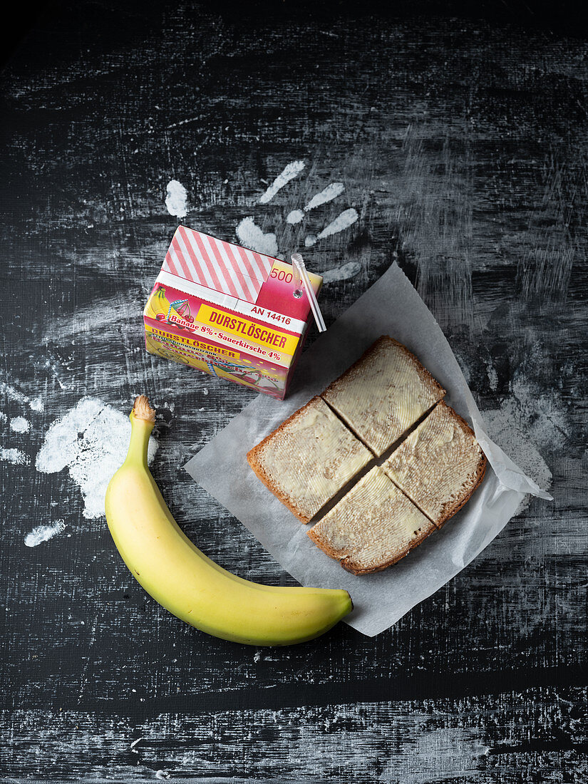 A sandwich, a banana and juice for a break