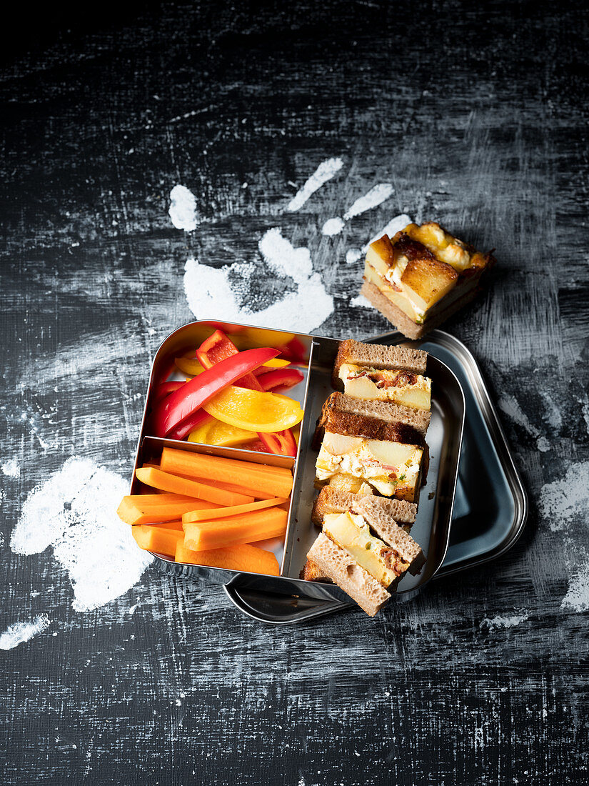 Frittata sandwiches and raw vegetables in a lunchbox