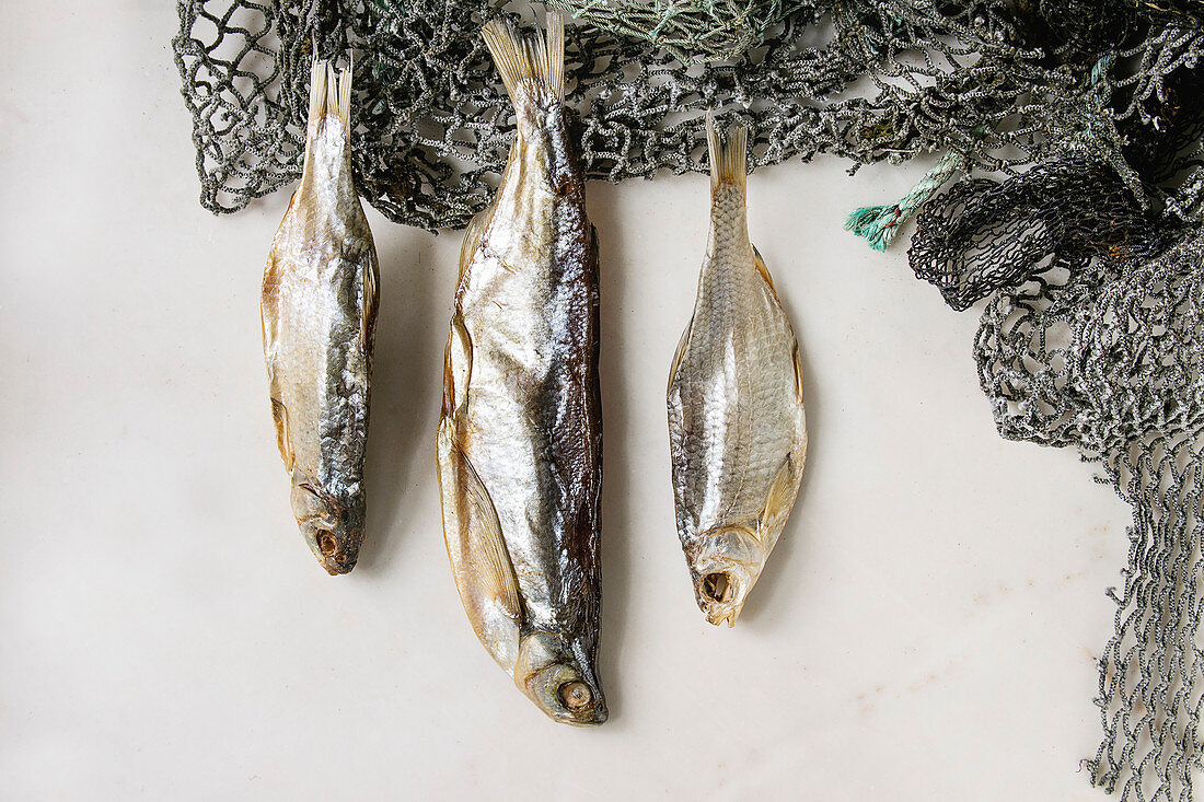 Dried fish or stockfish on fishing nets over white marble background