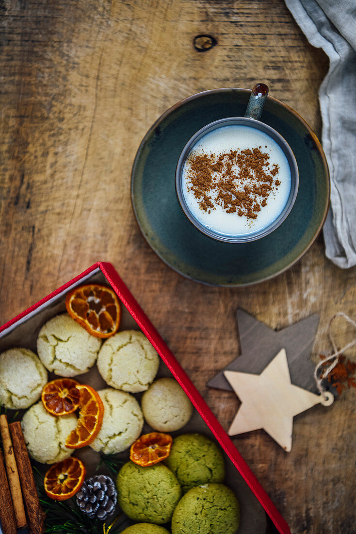 A cup of Turkish salep garnished with cinnamon powder, box full of cookies, cinnamon sticks and orange chips