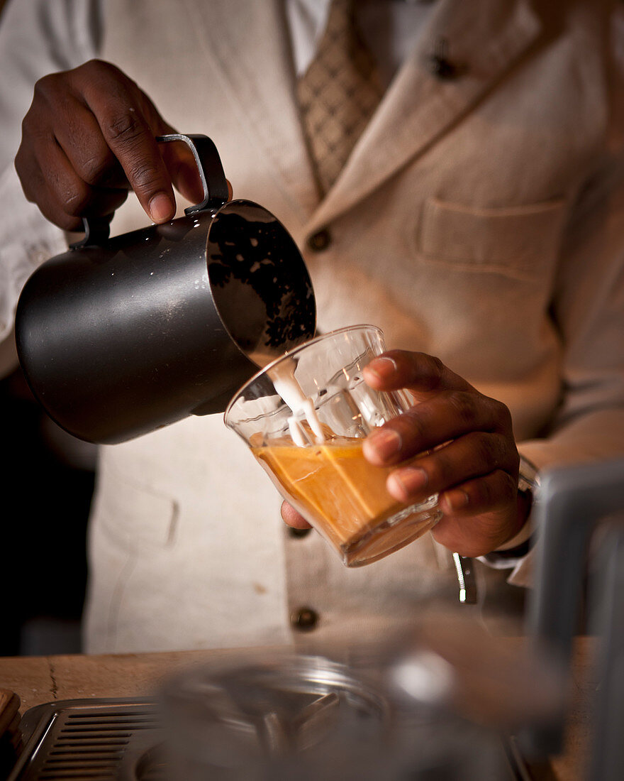 A barista pouring milk into a glass of coffee