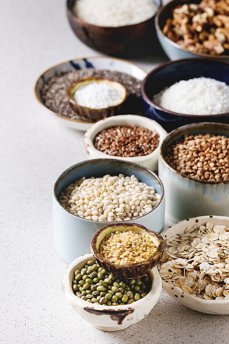 Variety of raw uncooked grains superfood cereal chia seeds, linen, sesame, mung bean, walnuts, tapioca, wheat, buckwheat, oatmeal, coconut and rice