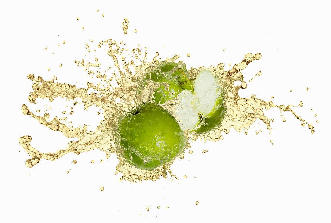 Green apples with an apple juice splash