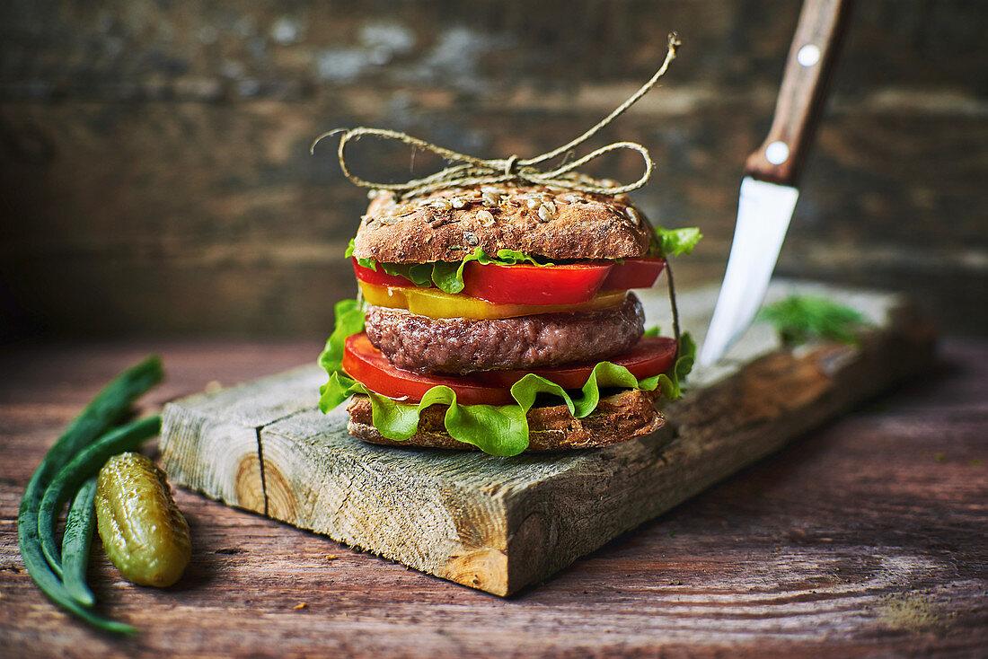 Tasty fresh burger tied with linen thread lying on shabby lumber board