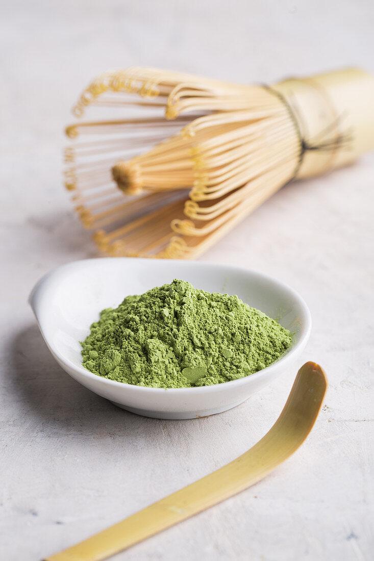 Green matcha tea powder and bamboo whisk
