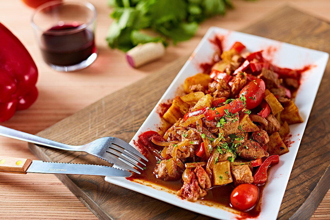 Gourmet dish with meat, potato and vegetables served with red sauce