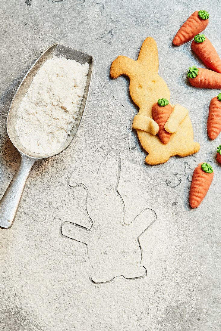 Easter Bunny biscuits with marzipan carrots and a scoop with flour