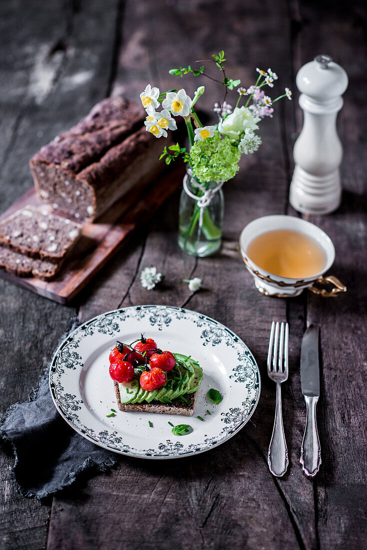 Hazelnut bread with avocado slices and tomatoes, and a cup of tea