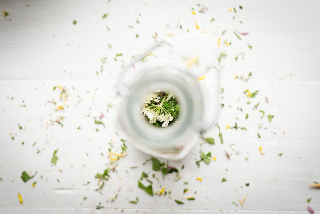 Chopped wild herbs in a glass bottle