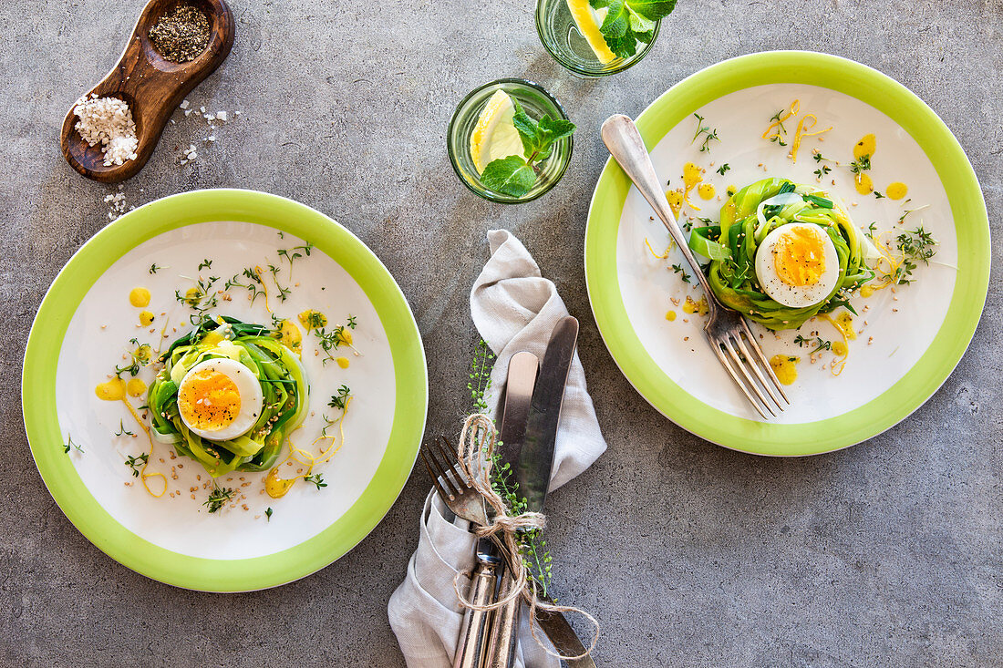 Boiled eggs in leek nests with lemon dressing, sesame seeds and cress