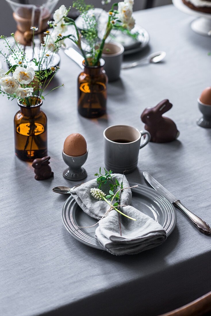 A table laid for an Easter breakfast with a boiled egg, coffee and chocolate bunnies
