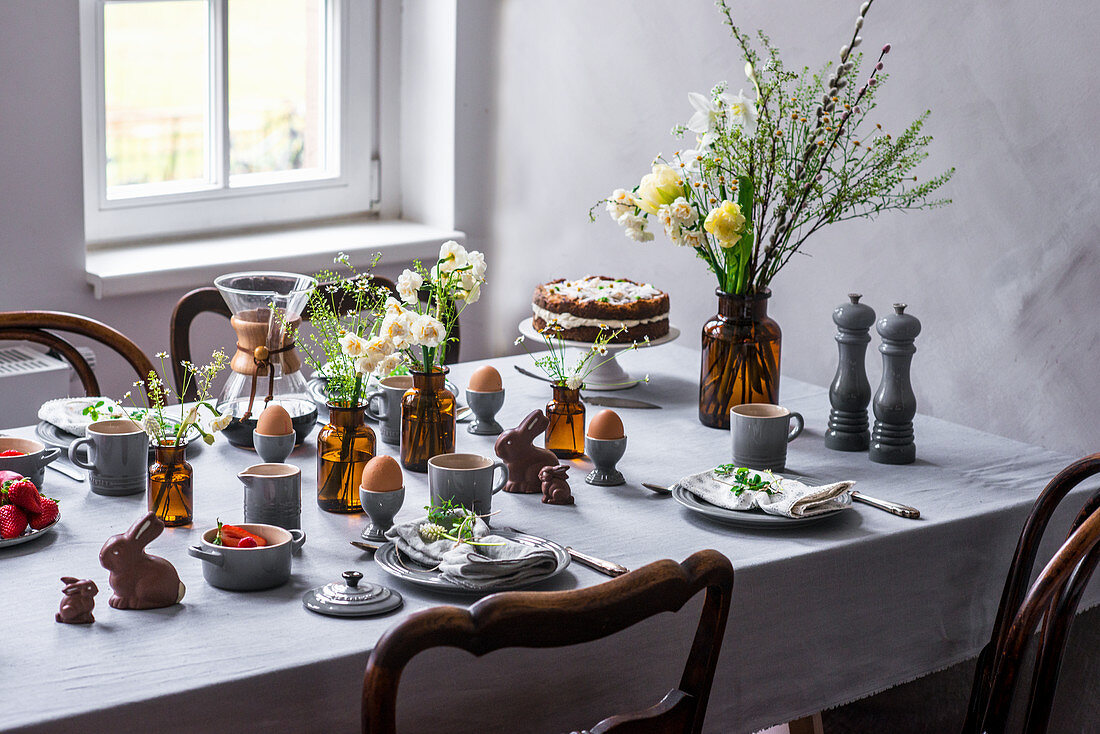 A table laid for an Easter breakfast with boiled eggs, coffee, carrot cake, chocolate bunnies and fruit salad