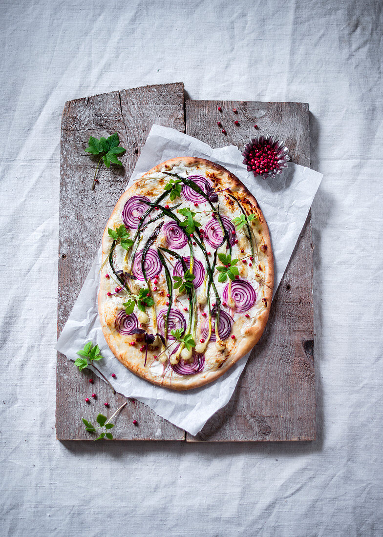 Tarte flambée with wild garlic, red onions, pink pepper and ground-elder