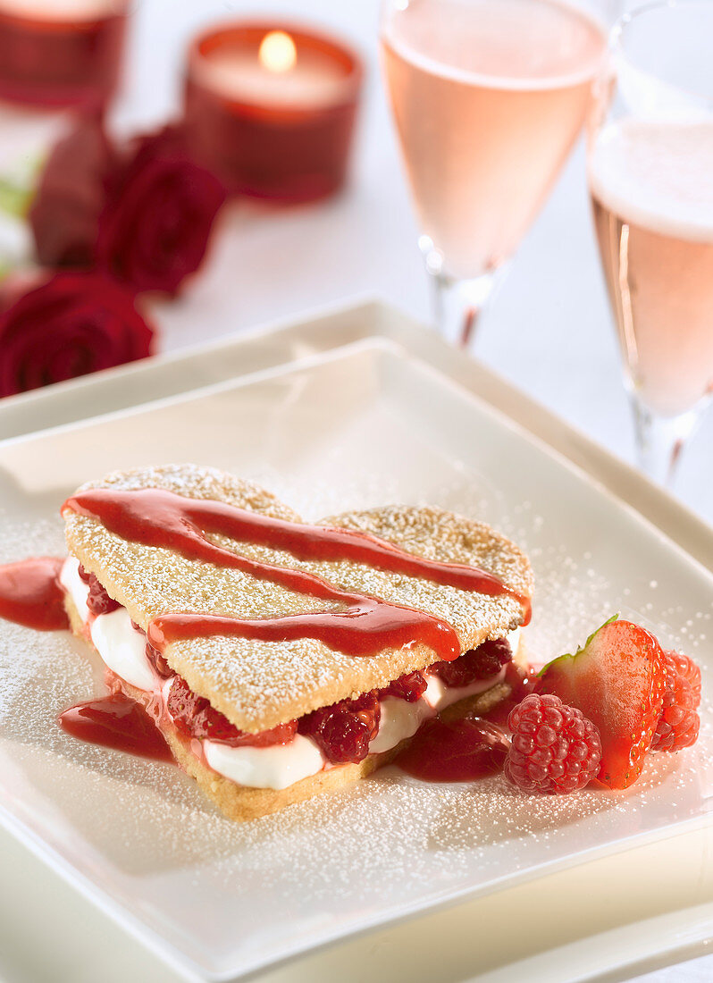 Romantic dessert for two on Valentine's Day with heart shaped shortbread sandwiched with cream and raspberries