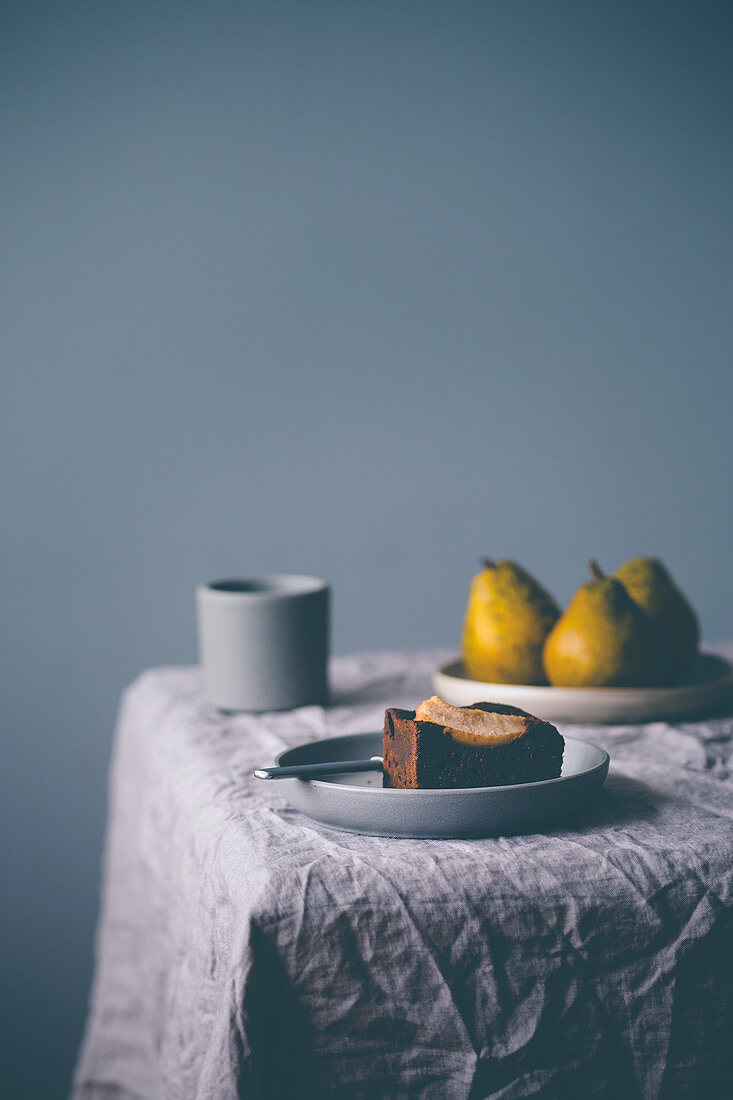 Plate with piece of a pear brownie, on a table