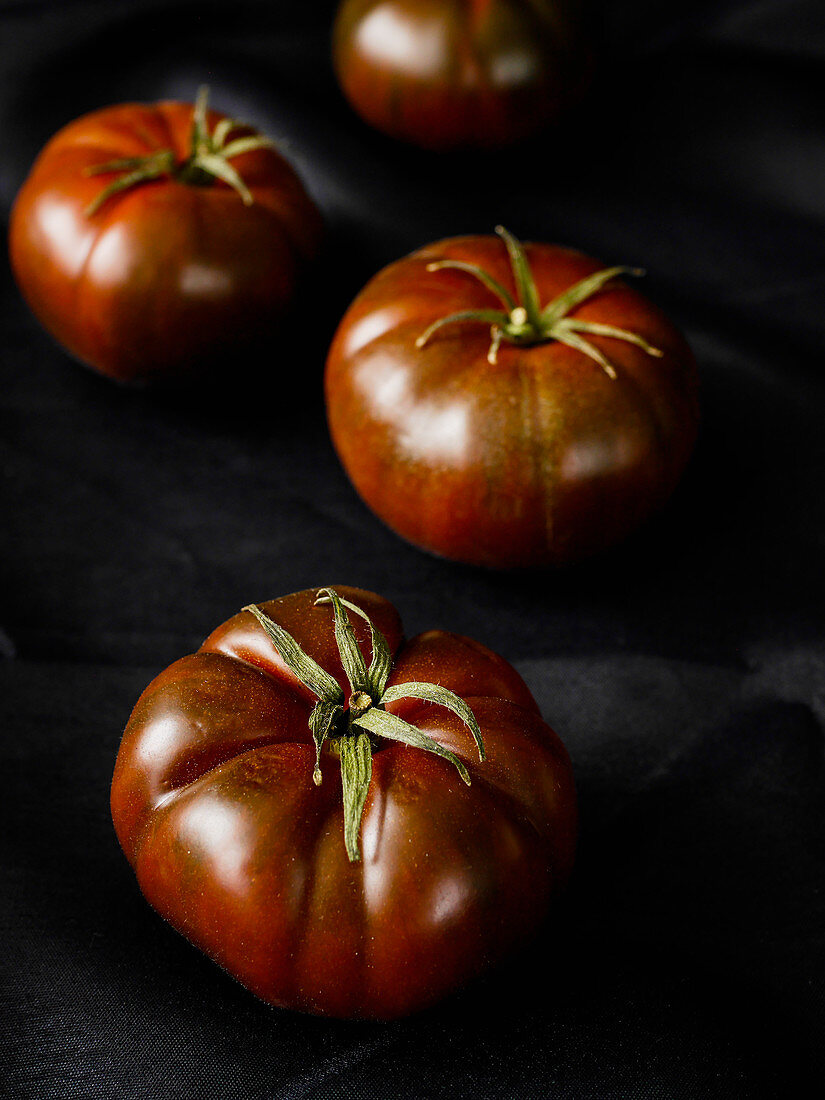 Brown tomatoes on a black surface