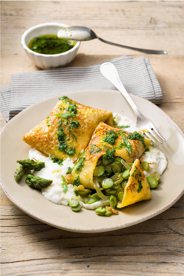 Corn pancakes with green asparagus, stacchio sauce and rocket oil