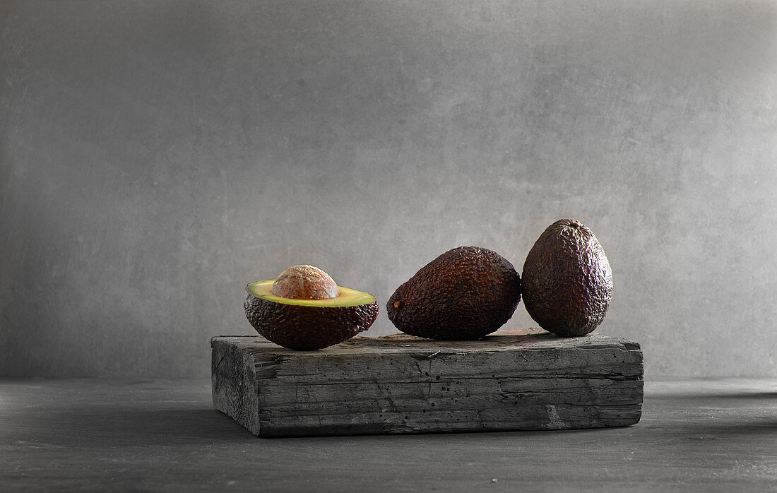 Two whole and one halved avocado on a wooden board