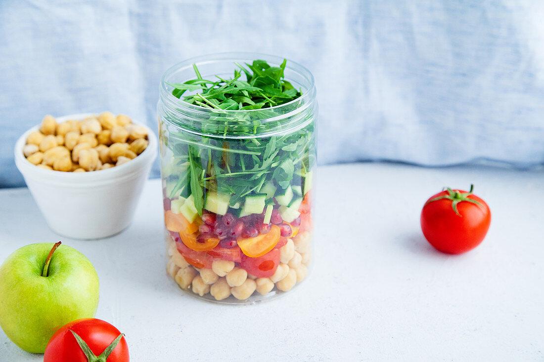 Gesunder Salat mit Kichererbsen und Rucola im Glas zum Mitnehmen