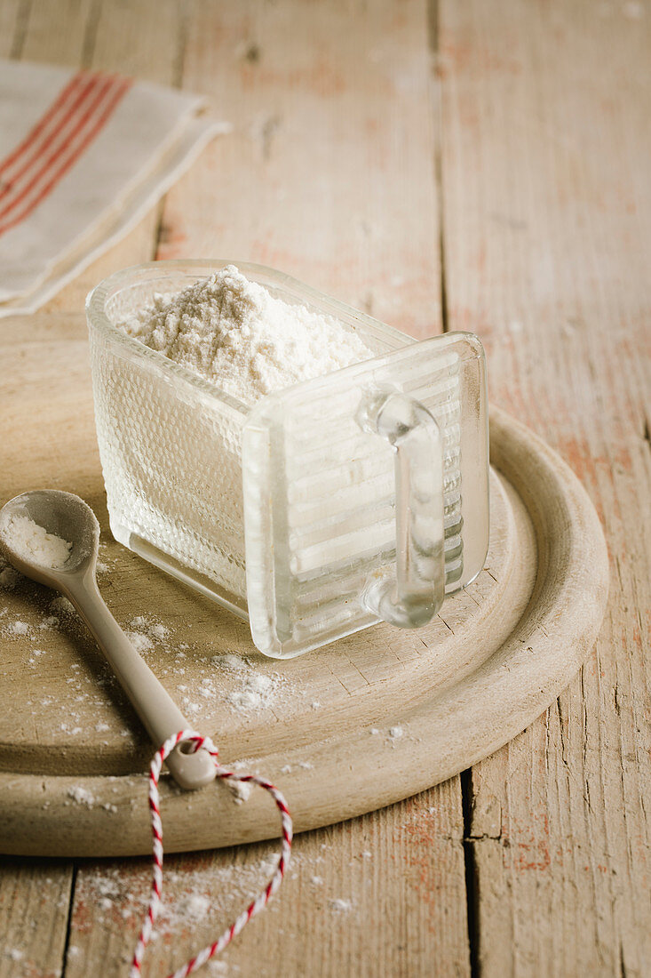 Flour in a glass container on a wooden plate with a porcelain spoon