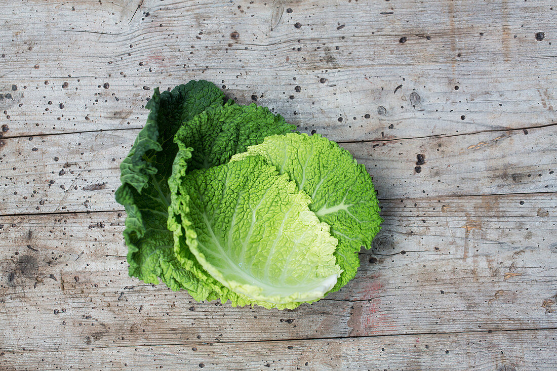 Savoy cabbage leaves on a wooden surface