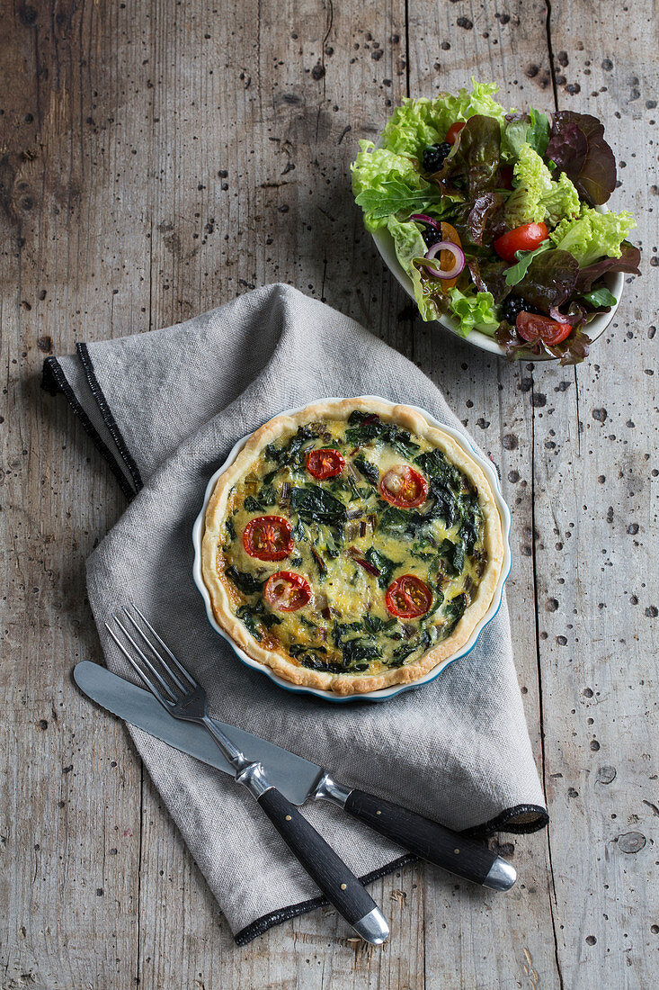 Chard quiche with tomatoes served with a side salad