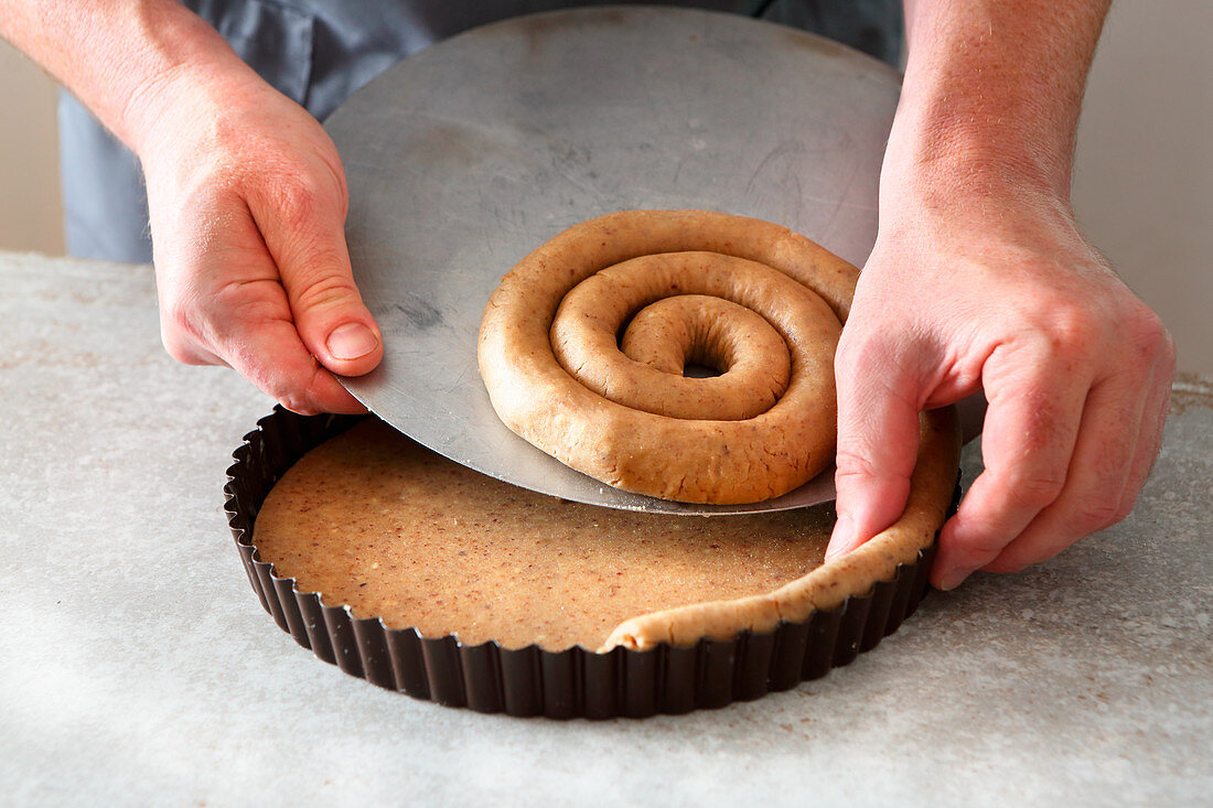 Linzertorte (nut and jam layer cake) being made: pastry edge being placed in a baking tin