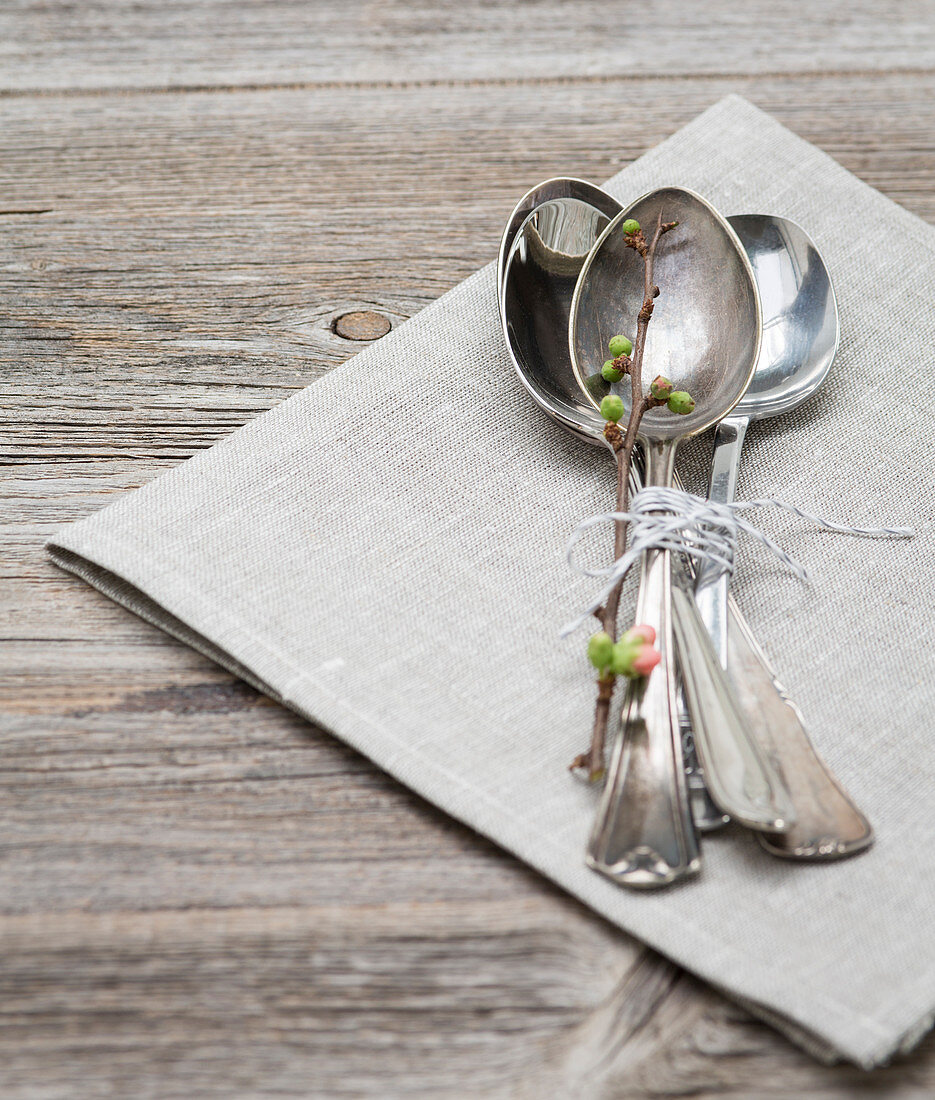 A bundle of spoons with a spring twig