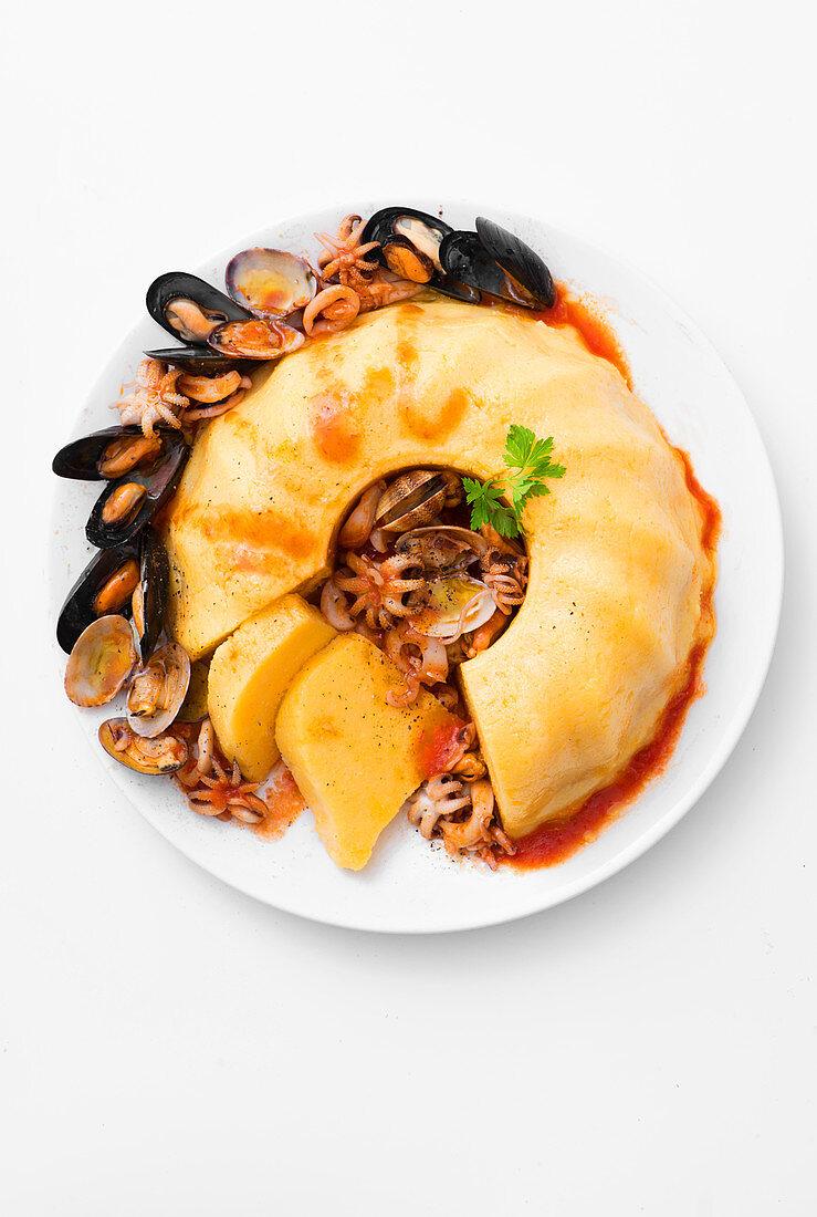 Polenta cake with various seafood
