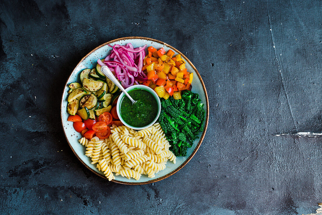A plate with pasta, steamed kale, roasted peppers and zucchini, cherry tomatoes and pickled onions, served with kale pesto