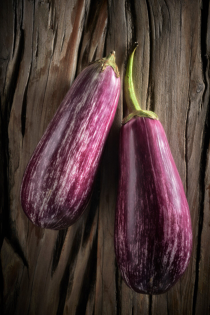 Two purple striped aubergines on a wooden background
