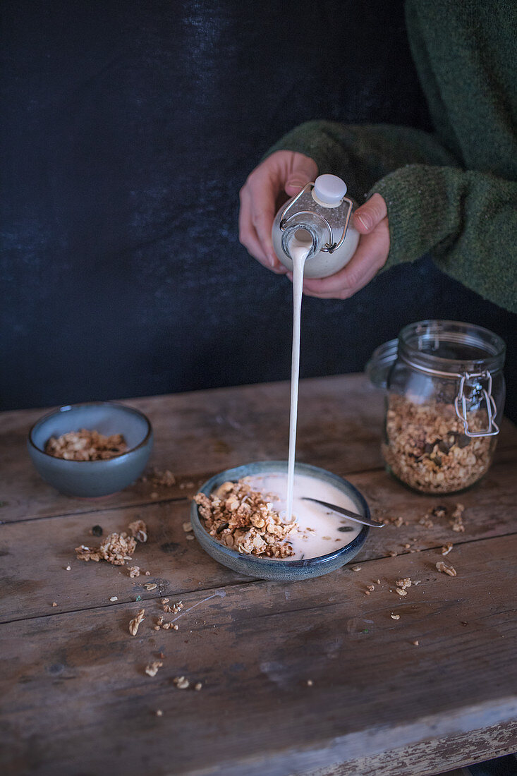A person pouring milk into a bowl of muesli