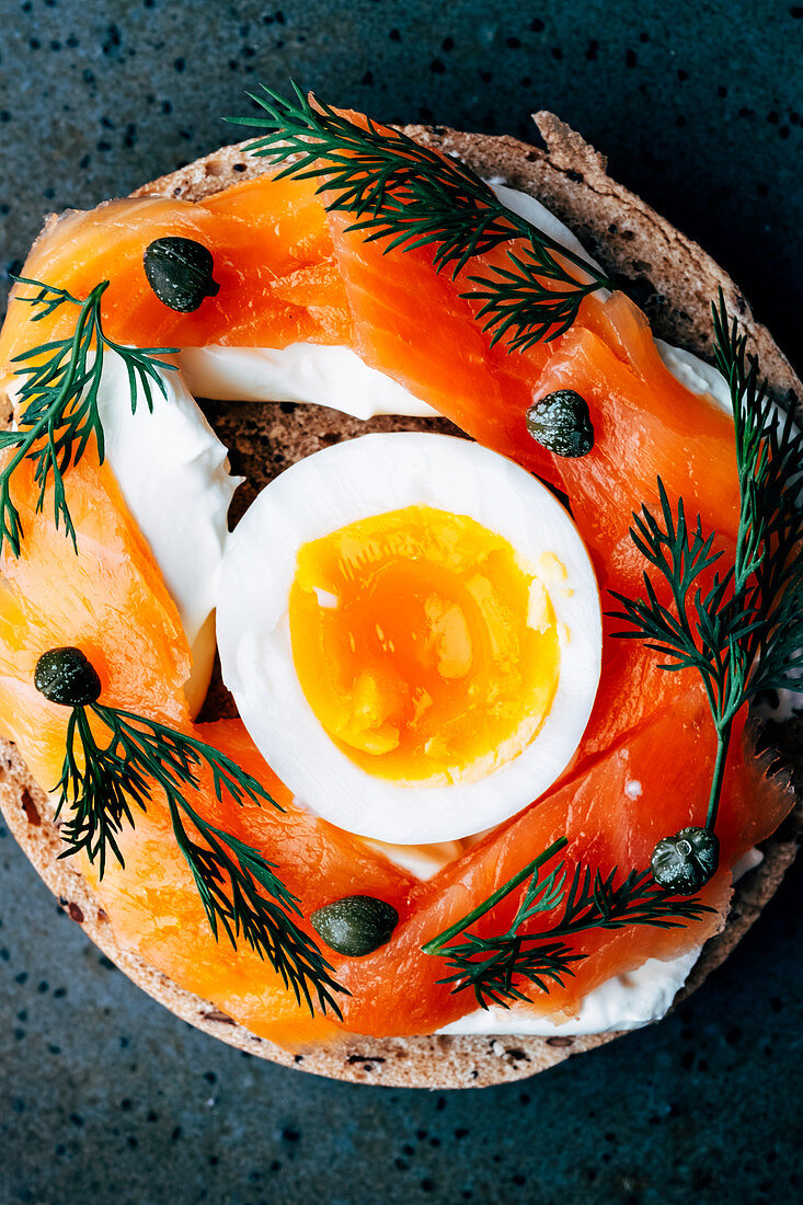 Smoked salmon multigrain bagel with creme fraiche, egg, capers and dill