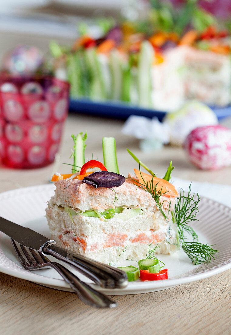 A slice of savoury cake with salmon and vegetables on a plate
