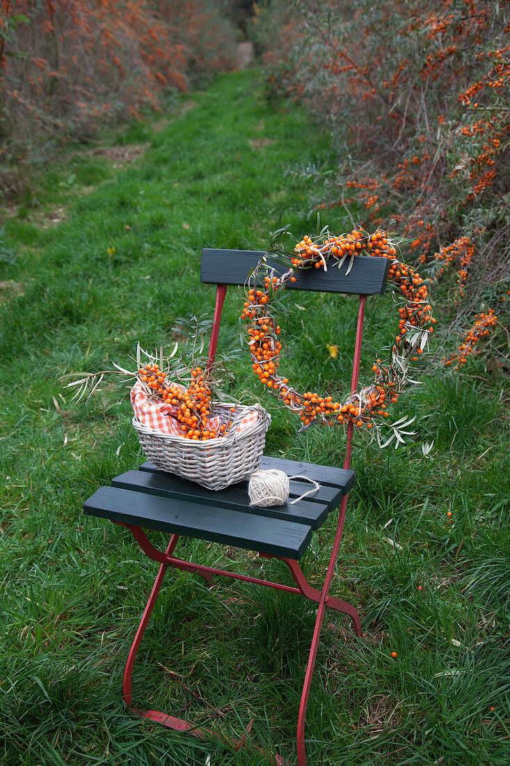 Homemade sea-buckthorn wreath and sea-buckthorn branches in a basket