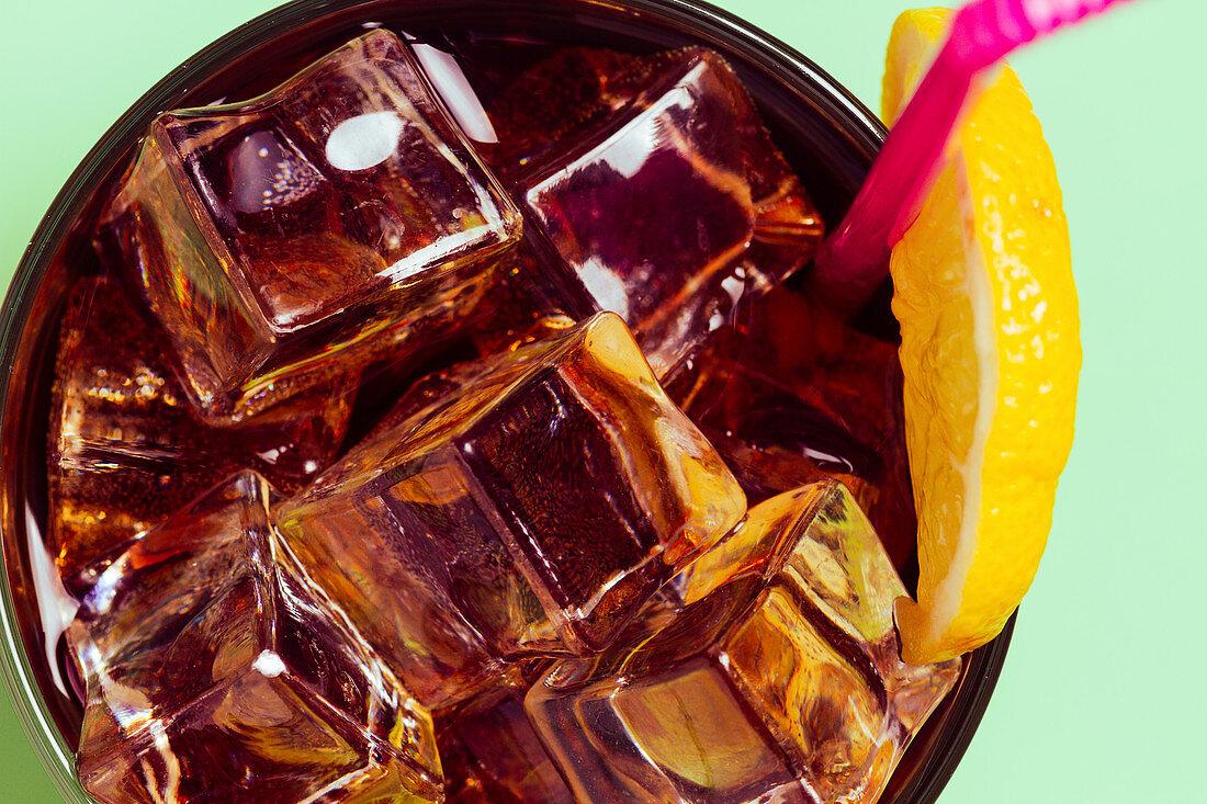Cola im Glas mit Eiswürfeln und Zitrone