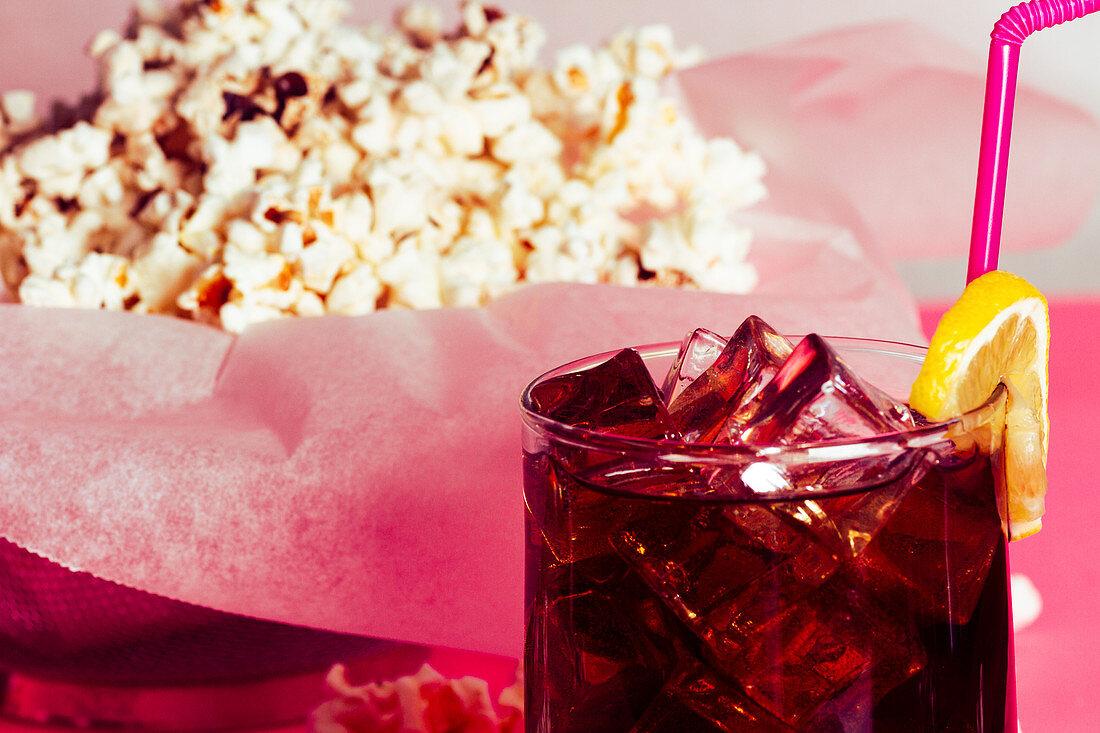 Cola im Glas mit Eiswürfeln und Zitrone vor einem Haufen Popcorn