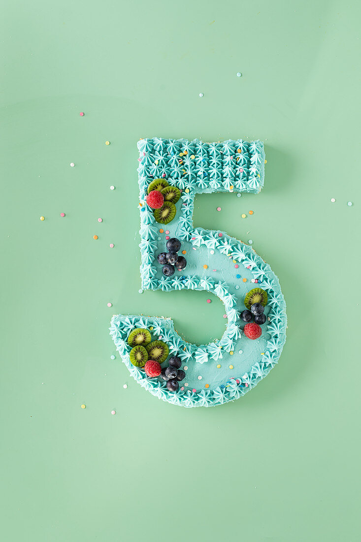 A blue cream cake decorated with fruit for a 5th birthday