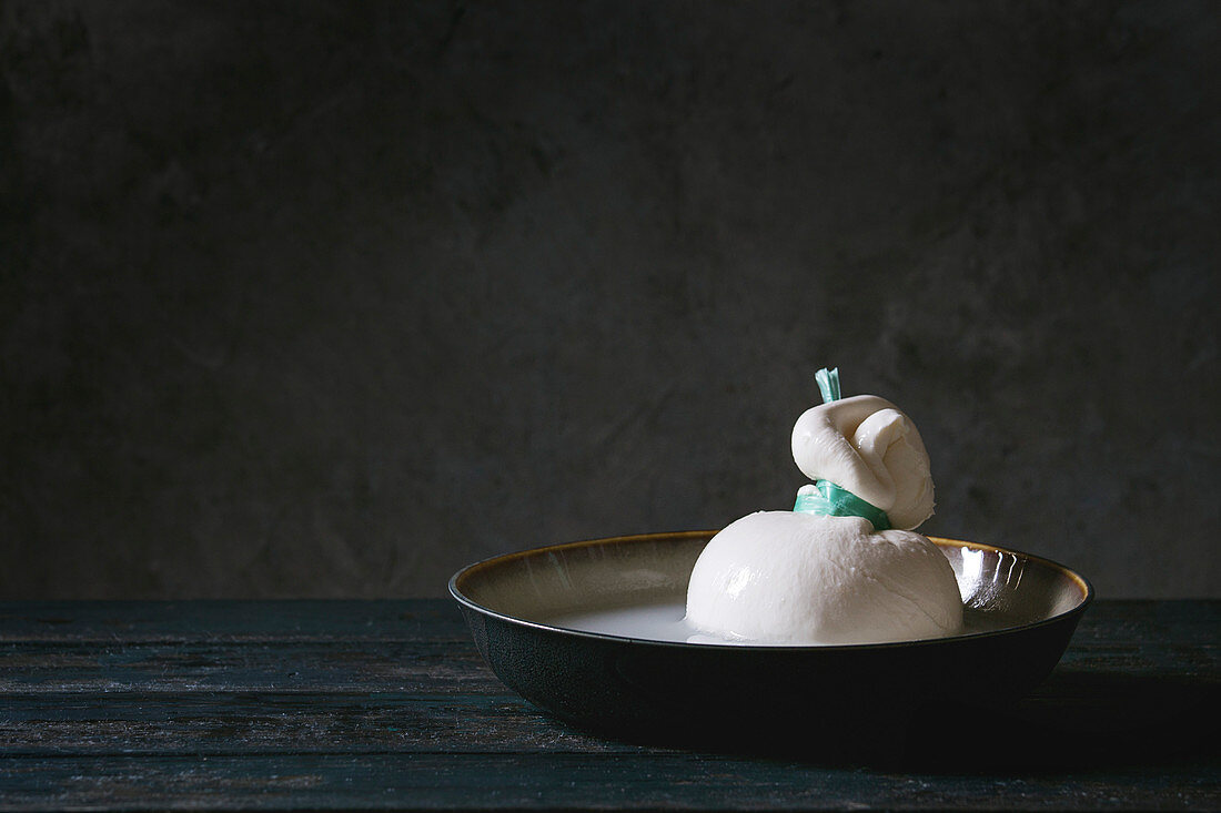 Bowl with whole tied Italian cheese burrata in brine on wooden plank table