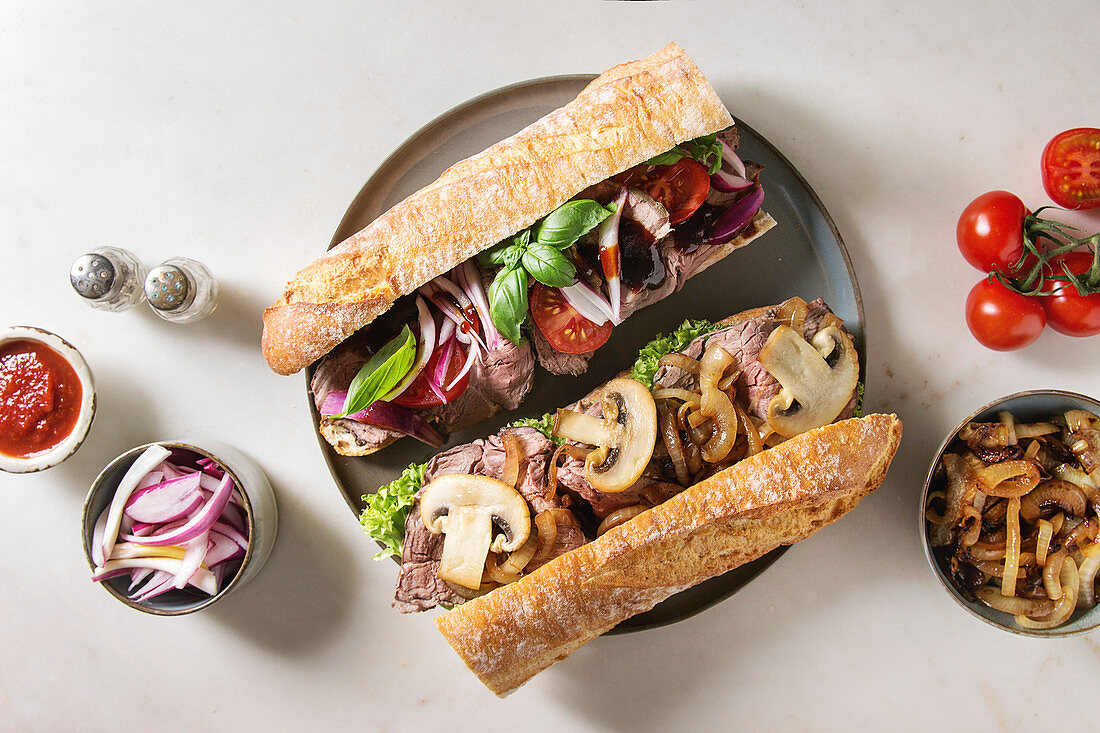 Variety of beef baguette sandwiches with champignon mushrooms, green salad, fried onion and tomatoes