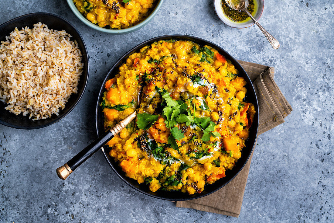 Vegan dal with red lentils, squash, chickpeas and spinach in a bowl with rice on the side (India)