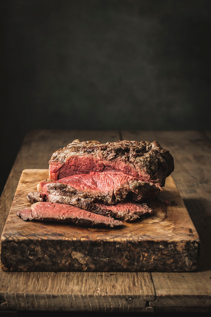 Juicy fresh cooked roast beef on rough cutting board on table