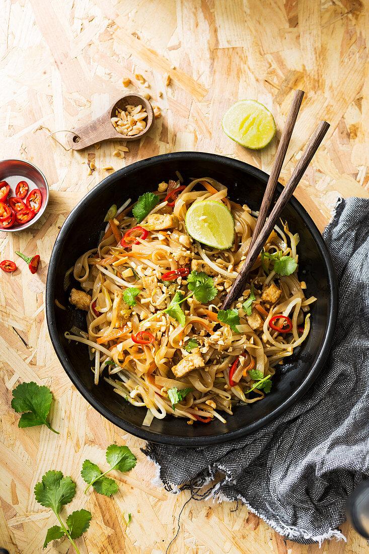 Dark Bowl of Thai street food, tofu, noodles and vegetable