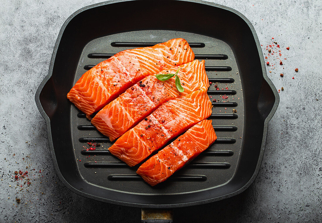Fresh raw salmon fillet garnished with green basil leaves on grill skillet