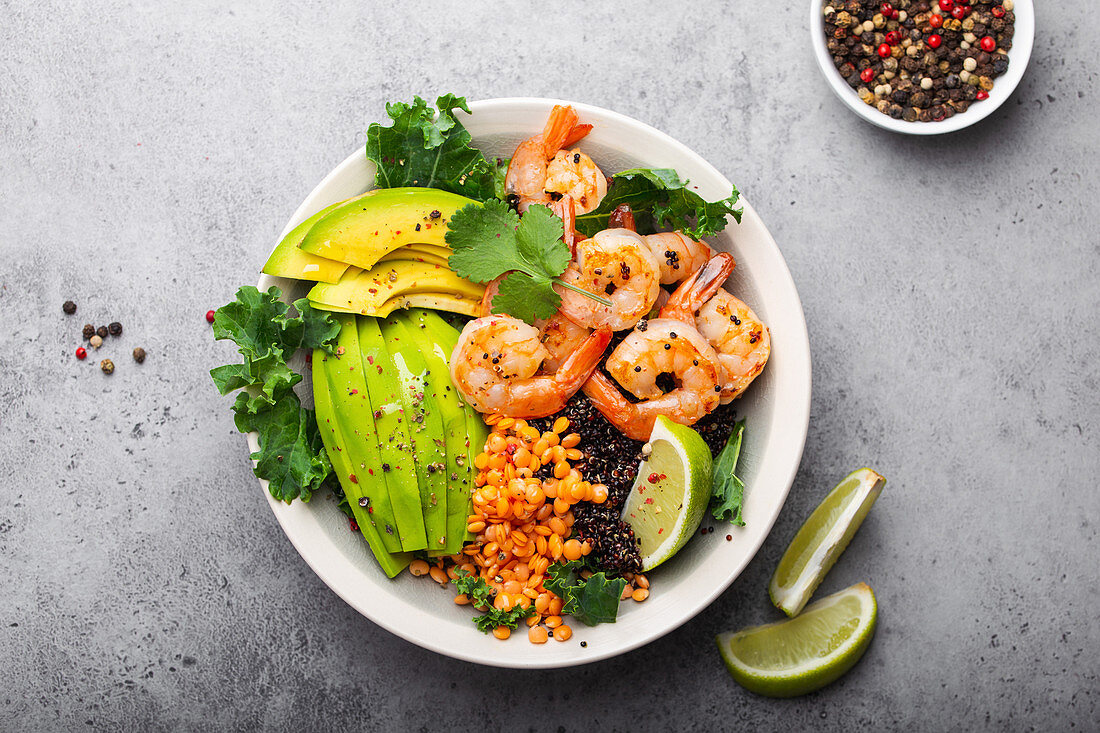 Salad bowl with shrimps, avocado, fresh kale, quinoa, red lentils, lime and olive oil