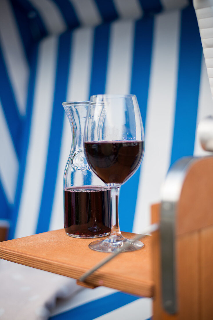 A glass of red wine and a carafe of wine in a beach chair