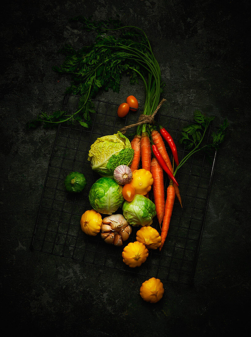 An arrangement of vegetables featuring cabbage, patty pan squash, carrots, garlic and tomatoes