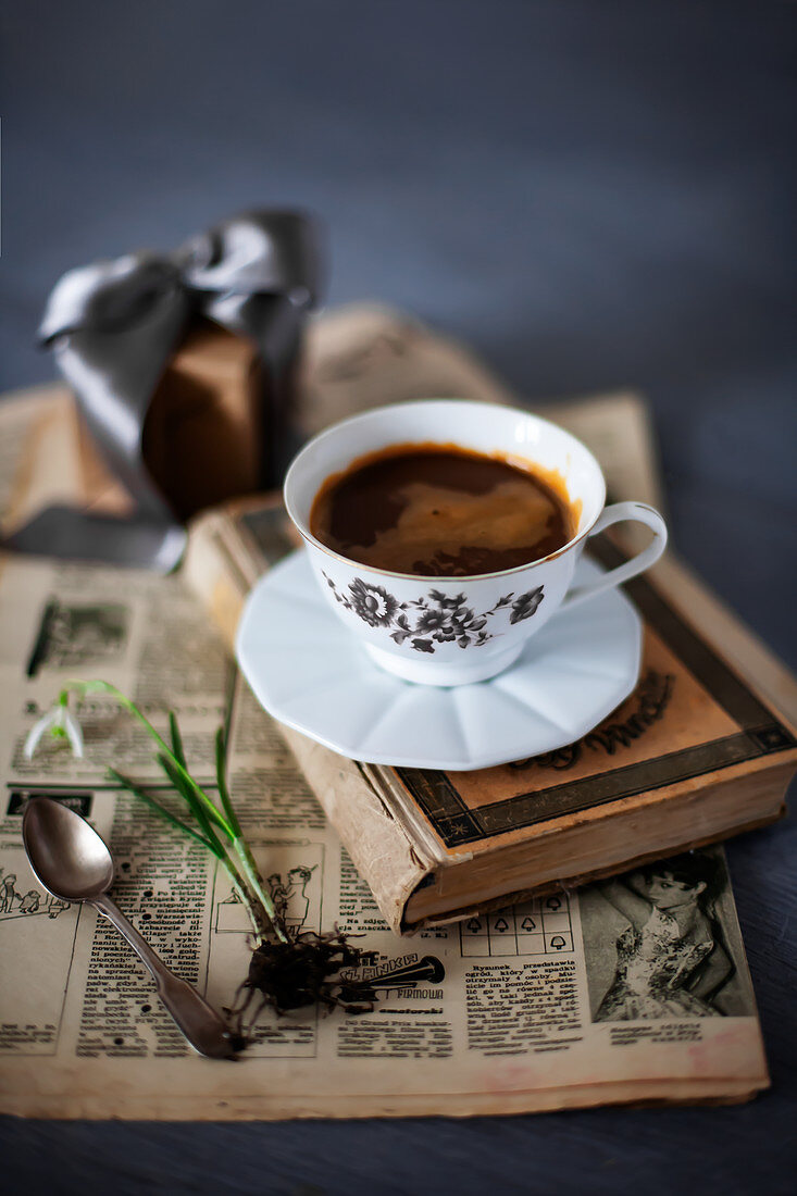 Old newspaper, book, cup of coffee and flower