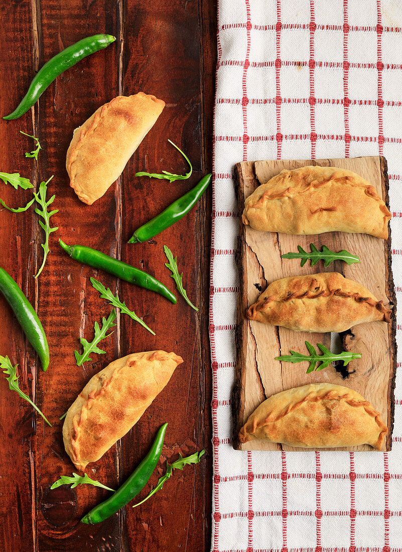 Empanada Patties between green plant and chili pepper